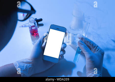 Scientist Examining Chemical While Using Mobile Phone In Laboratory