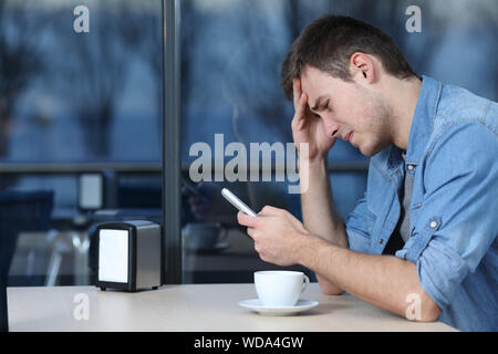 Side view portrait of a sad man checking mobile phone message in a coffee shop - Stock Photo