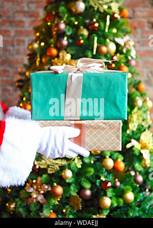 Santa Claus secretly putting gift boxes by the Christmas tree. Xmas - Stock Photo