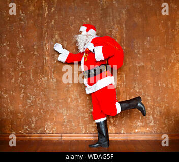Santa Claus walking with the big red bag of the presents on the brown background - Stock Photo
