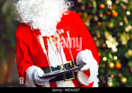 Santa Claus holding champagne glasses on the tray. Closeup - Stock Photo