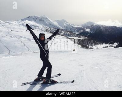 Happy Woman Gesturing While Skiing On Snowy Field By Mountains Against Sky - Stock Photo