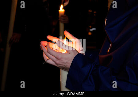 Closeup of the hands of a nazarene penitent during a nocturnal procession holding his candle. Holy Week of Seville, Andalusia, Spain - Stock Photo