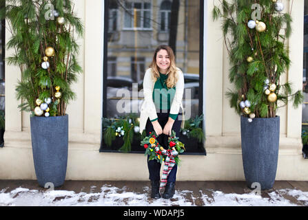 Happy woman holding Christmas wreath maked by herself - Stock Photo
