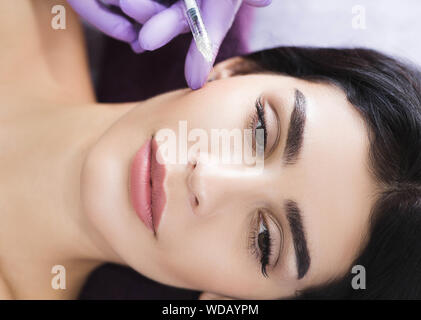 Cosmetic face treatment. Beautiful mid aged woman getting face injection, anti wrinkles effect, beauty injections for skin and face rejuvenation - Stock Photo