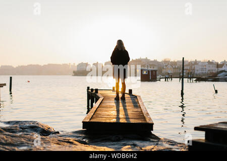 Silhouette of woman standing on jetty at sunset - Stock Photo