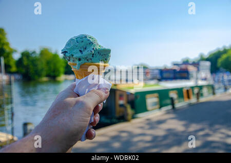 A male hand holding a cone of  mint and choc chip ice cream - Stock Photo