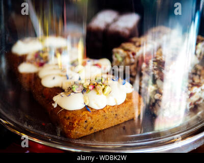 Close-up Of Pastries In Glass Container At Coffee Shop - Stock Photo