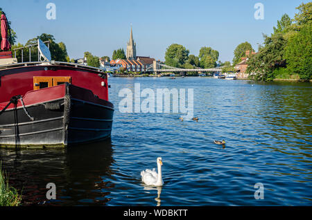 A red narrowboat moored on the bank of The River Thames next to the Thames Path. In the distance is the centre of Marlow and the Marlow bridge. - Stock Photo