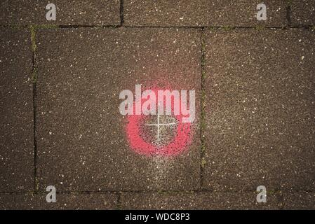 Directly Above Shot Of Plus Sign And Red Circle On Street - Stock Photo