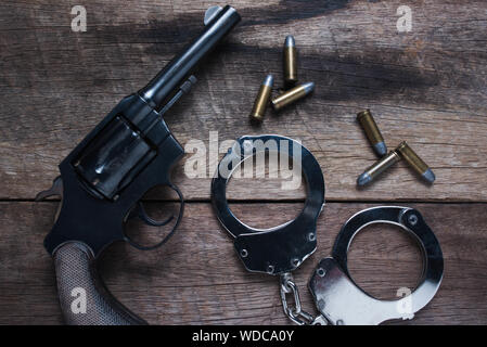 Gun with ammunition and shackle on wood background, Top view - Stock Photo