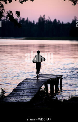 Rear View Of Silhouette Boy Running On Pier Over Lake During Sunset - Stock Photo