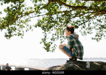Boy crouching under tree - Stock Photo