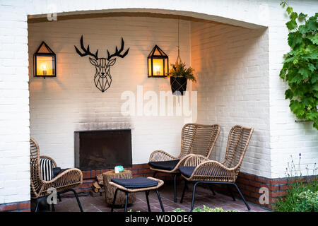 outdoor lounge set in a green garden in the alcove of a white painted building - Stock Photo