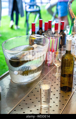 Festive bottles of wine in a cooler at the bar during a luxury garden party in the summer - Stock Photo