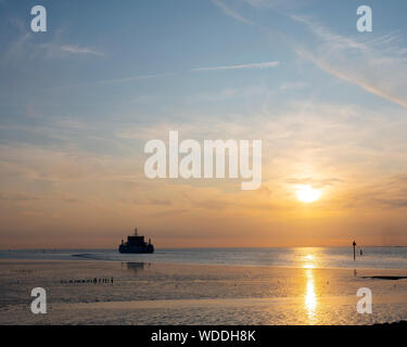 ferry from ameland arrives during sunset at harbor of Holwerd in dutch province of friesland - Stock Photo
