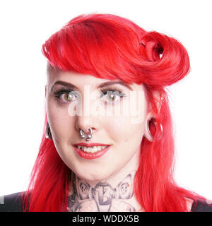 young woman with facial piercings and tattoos - Stock Photo