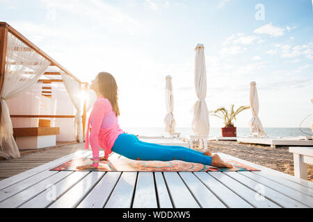 Woman doing yoga outside in a garden on a wooden floor. - Stock Photo