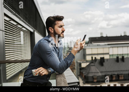 Young man looking at cell phone on balcony - Stock Photo