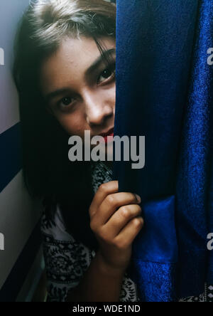 Portrait Of Smiling Teenage Girl Sitting Behind Curtains - Stock Photo