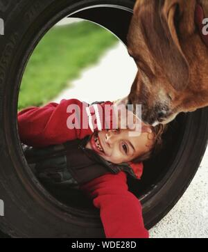 Portrait Of Happy Boy Playing With Tire By Dog On Footpath - Stock Photo