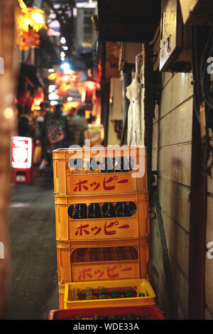 Stacked emptied bottles in yellow containers at Omoide Yokocho food alley near Shinjuku. - Stock Photo