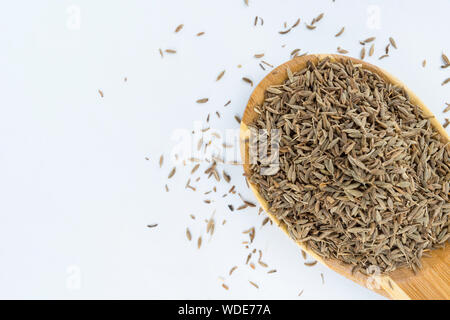 Close-up Of Cumin Seeds In Wooden Spoon Over White Background - Stock Photo