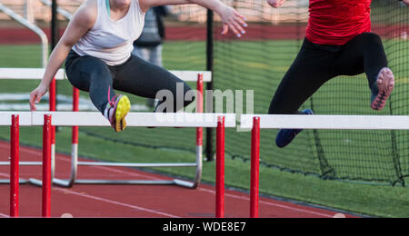 Two high school girls racing each other in the hurdles during a track and field race. - Stock Photo