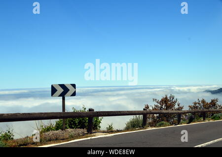 Road Sign By Fence Against Clear Blue Sky - Stock Photo