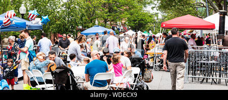 Babylon, New York, USA - 1 June 2019: Families and shoppers sitting at tables and strolling around the streets of Babylon Village during a street fair - Stock Photo