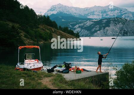 A beautiful shot of a kid near bags holding a fishing pole with the sea and mountains in the background - Stock Photo