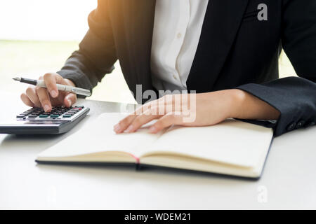 Midsection Of Businesswoman Using Calculator In Office - Stock Photo