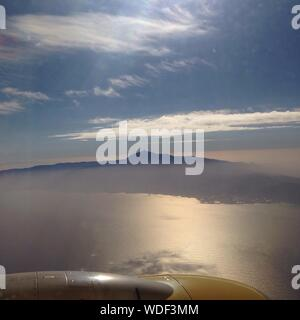 Scenic View Of El Teide Volcano Against Sky Seen From Cropped Airplane Flying Over Sea - Stock Photo