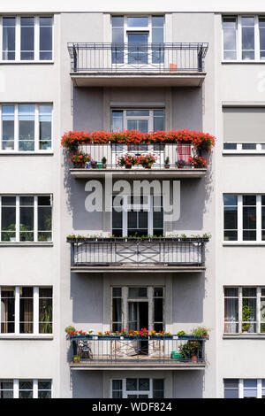 Floral displays on the balconies of an apartment building in the city of Warsaw, Poland. - Stock Photo