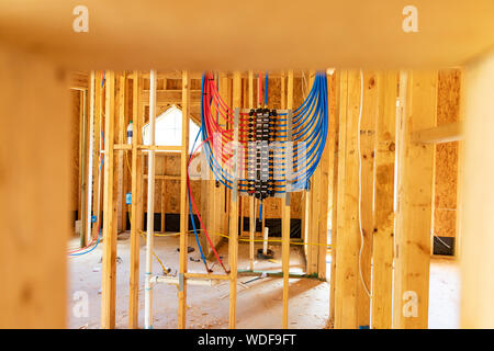 PEX plumbing manifold for water distribution in new home construction. Selective focus - Stock Photo