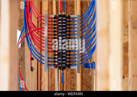 PEX plumbing manifold for water distribution in new home construction, selective focus - Stock Photo