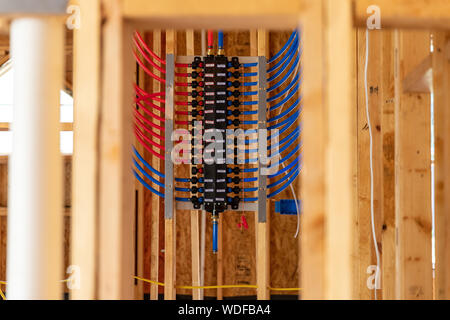 PEX plumbing manifold for water distribution in new home construction, selective focus. - Stock Photo