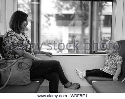 Smiling Mother And Daughter Sitting By Window While Traveling In Cable Car - Stock Photo