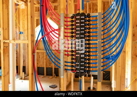 PEX plumbing manifold for water distribution in new home construction - Stock Photo