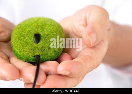 Close-up Of Man Holding Computer Mouse With Grass - Stock Photo