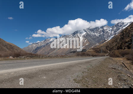 Georgia, Military Road in spring with mountain, glacier and a small village in sight, blue sky - Stock Photo