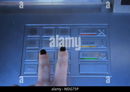 Cropped Image Of Woman Operating Atm Machine - Stock Photo