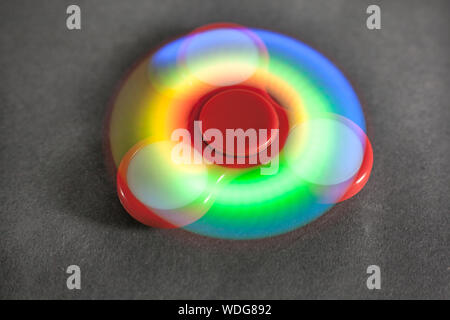 Close-up Of Illuminated Colorful Fidget Spinner Spinning On Table - Stock Photo