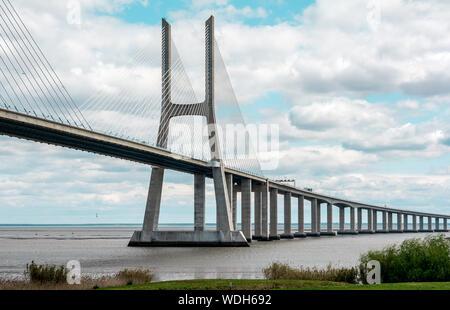 Vasco Da Gama Bridge Over River Against Cloudy Sky - Stock Photo