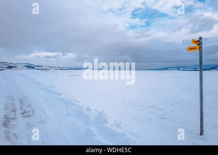 Directional Sign On Snow Covered Road Against Cloudy Sky - Stock Photo
