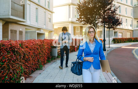 Serious businesswoman walking down the street towards her work while a businessman walks behind. Selective focus on woman in foreground - Stock Photo