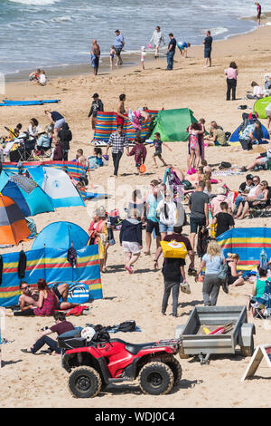 Holidaymakers on a staycation holiday enjoying themselves on Fistral Beach in Newquay in Cornwall.