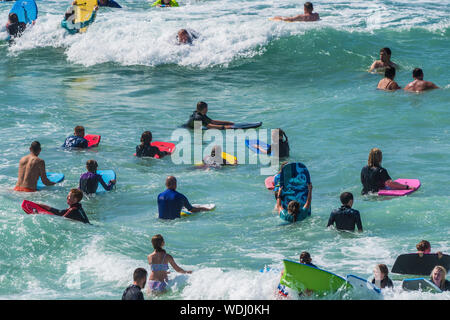 Holidaymakers on a staycation holiday enjoying themselves in the sea at Fistral in Newquay in Cornwall.