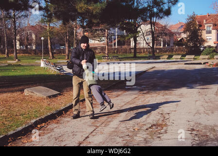 Father Playing With Son On Road In City - Stock Photo
