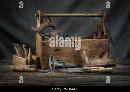 Still life - Old Wooden vintage toolbox with hammers, saw, chisels, plane and pliers in carpentry - Stock Photo